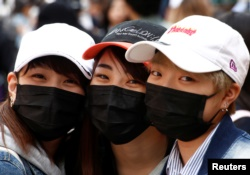 Japanese women wearing masks to prevent pollen allergy and for fashion, pose for photographs at Harajuku shopping district in Tokyo, Japan March 15, 2018. (REUTERS/Kim Kyung-Hoon)