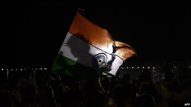 A spectator holds an Indian flag after a mission of Indian Space Research Organization's Chandrayaan-2, with the Geosynchronous Satellite Launch Vehicle on board was called back because of a technical snag in Sriharikota, India, July 15, 2019.
