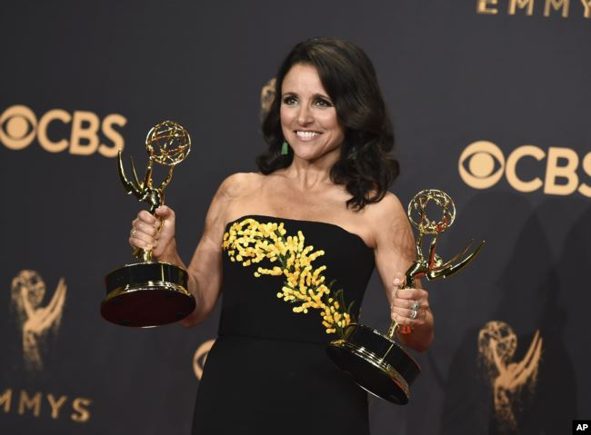 FILE - Julia Louis-Dreyfus poses in the press room with her awards for outstanding lead actress in a comedy series and outstanding comedy series for 'Veep' at the 69th Primetime Emmy Awards at the Microsoft Theater in Los Angeles, Sept. 17, 2017.