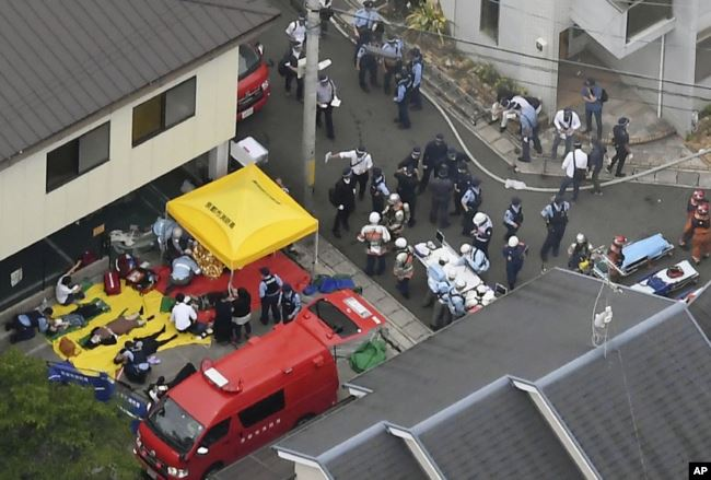 People injured in a fire are treated near a Kyoto Animation building in Kyoto, western Japan, Thursday, July 18, 2019. The fire started in the three-story building after a suspect poured an unidentified liquid and set the fire.