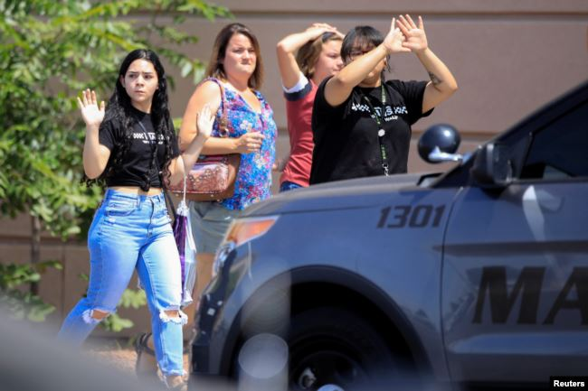 People leaving the shopping area of a mass shooting at a Walmart in El Paso, Texas.