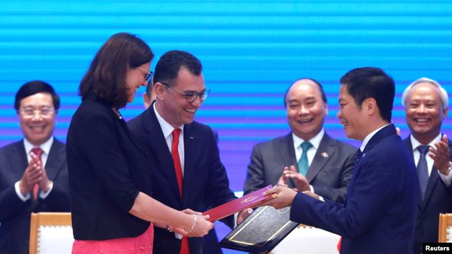 European Commissioner for Trade Cecilia Malmstrom, Romania's Business, Trade and Enterpreneurship Minister Stefan Radu Oprea and Vietnam's Industry and Trade Minister Tran Tuan Anh exchange documents while attending the signing ceremony of EU-Vietnam Free