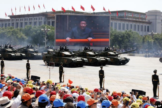 In this Thursday, Sept. 3, 2015 file photo, Chinese President Xi Jinping is displayed on a big screen as Type 99A2 Chinese battle tanks roll across during a parade.