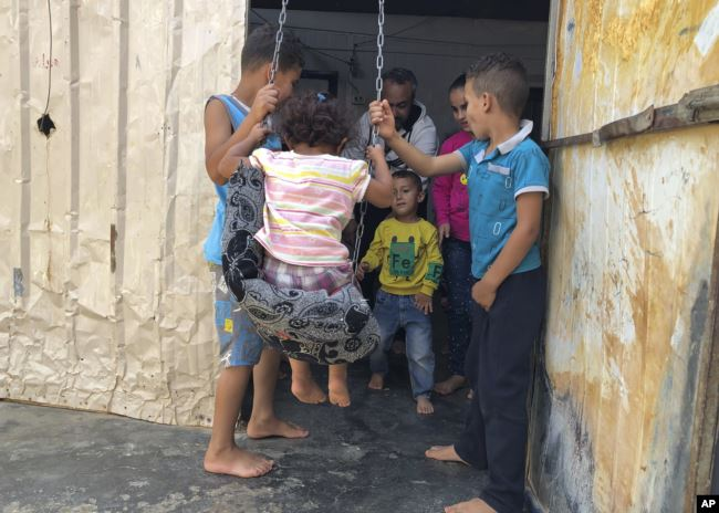 In this August 29, 2019 photo, Yousef Samara, a 42-year-old refugee from Syria's Deraa province plays with his children and nephews inside his caravan, in the Zaatari camp in northern Jordan. (AP)