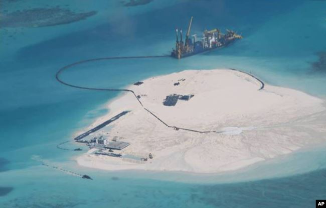 FILE - In this Feb. 25, 2014 photo taken by surveillance planes and released by the Philippine Department of Foreign Affairs, a Chinese vessel, top center, is used to expand structures and land on the Johnson Reef.