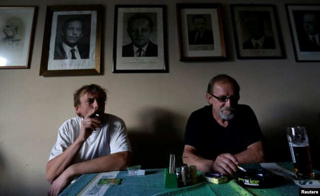 Men smoke cigarettes in a pub on a last day before a smoking ban comes into effect in Prague, Czech Republic, May 30, 2017.