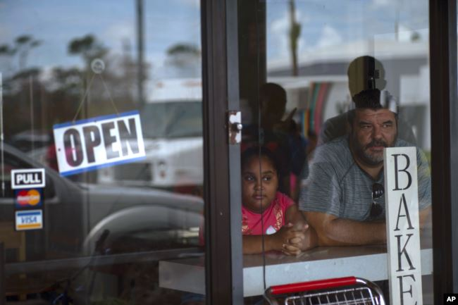 A man and girl peer out from a bakery and cafeteria in Freeport, Bahamas, Wednesday, Sept. 11, 2019. Those who survived Hurricane Dorian are facing the prospect of starting their lives over but with little idea of how or where to even begin. (AP Photo/Ram