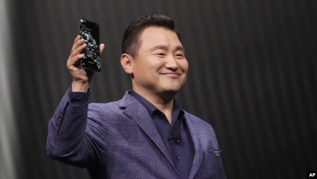 TM Roh, President and Head of Mobile Communications Business, holds a Samsung Galaxy S20 Ultra 5G phone while speaking at the Unpacked 2020 event in San Francisco, Tuesday, Feb. 11, 2020. (AP Photo/Jeff Chiu)