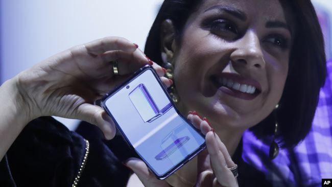 A woman holds a Samsung Galaxy Z Flip Phone displayed at the Unpacked 2020 event in San Francisco, Tuesday, Feb. 11, 2020. (AP Photo/Jeff Chiu)