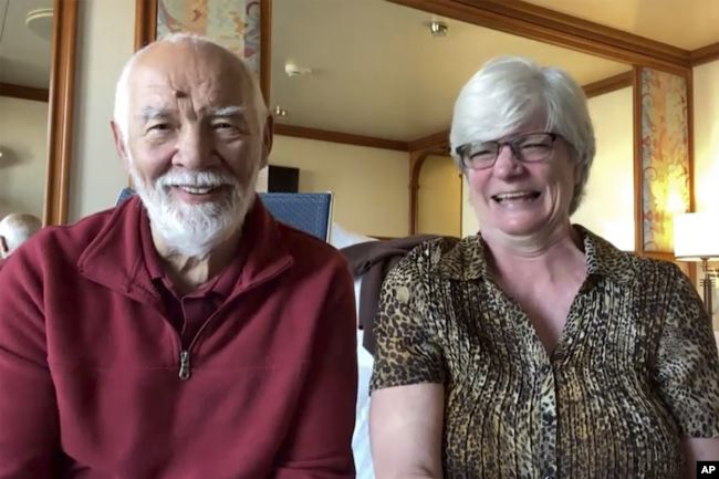 In this image from a video taken on Wednesday, Feb. 12, 2020, Paul Molesky and Cheryl Molesky are interviewed through Skype in their cabin room on the Diamond Princess, anchored at a port in Yokohama, near Tokyo.