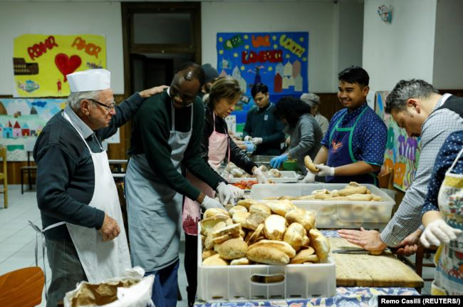 Dino Impagliazzo, Rome's 90-year-old 'chef of the poor', greets volunteers as they make sandwiches for the homeless living in the city.