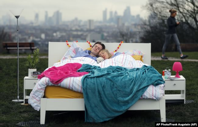 A couple lay in a double bed during a photo opportunity organised by the Mental Health Foundation to mark World Sleep Day, on Parliament Hill, in London, March 15, 2018.