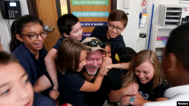 Joe Emery, TAC*ONE trainer and former Las Vegas police department sergeant, is swarmed by fifth grade students in a shooter take down exercise at Pinnacle Charter School during TAC*ONE training for an active shooter situation in a school in Thornton, Colo