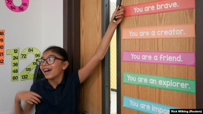 Fifth grade student Alondra Gomez shows how to tie a door shut in a exercise at Pinnacle Charter School during TAC*ONE training for an active shooter situation in a school in Thornton, Colorado, U.S. August 29, 2019.