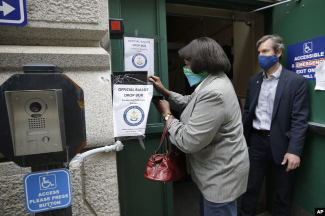 FILE - A voter, left, places a ballot in a secure box as Providence City Clerk Shawn Selleck, right, looks on, Tuesday, June 2, 2020, in Providence, R.I. More American voters asked for mail ballots during the coronavirus outbreak.