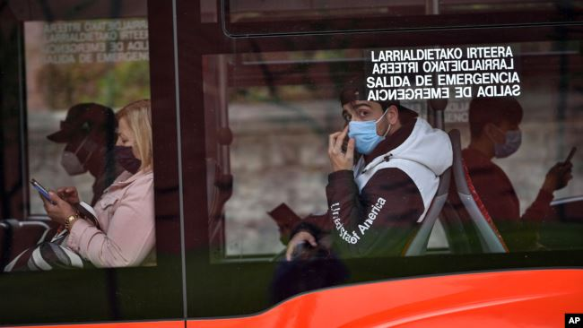 FILE - Passengers wearing face masks are seen on a bus in Bilbao, northern Spain, June 12, 2020.