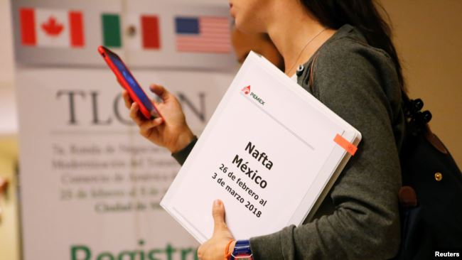 A member of the Mexican NAFTA negotiation team checks her phone during a lunch break in Mexico City, Mexico, Feb. 28, 2018.