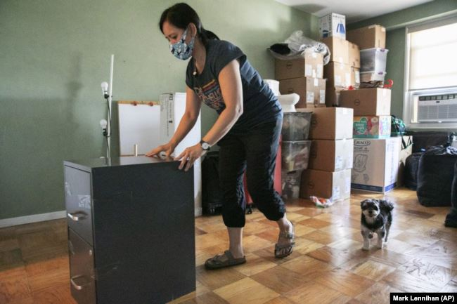 Joyce Lilly moves a filing cabinet as her dog Max follows, Tuesday, July 21, 2020, in the Riverdale neighborhood of The Bronx, in New York.