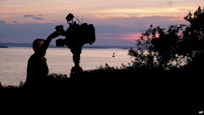 A member of a TV crew adjusts their camera while filming near the shore of Bailey Island, Maine, where a woman swimming off the coast was killed in an apparent shark attack Monday, July 27, 2020. (AP Photo/Jim Gerberich)