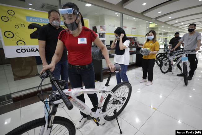 Benjamin Canlas Courage to be Kind Foundation founder Dr. George Canlas (left) watches as one of the winners pushes a bicycle during the award ceremony in Manila, Philippines, July 11, 2020.