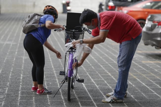 A winner, left, of a bicycle from the Benjamin Canlas Courage to be Kind Foundation prepares to ride. Photo taken in the financial district of Manila, Philippines, July 11, 2020.