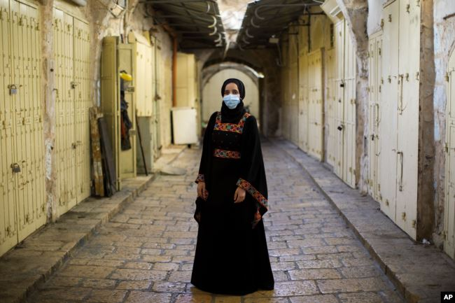 Israeli Arab Rana Hijazi,19, poses for a portrait wearing her protective face mask in the alleys of Jerusalem's old city, Tuesday, July 21, 2020. Hijazi says 'she advice all people to wear face masks because it is very important for their health.