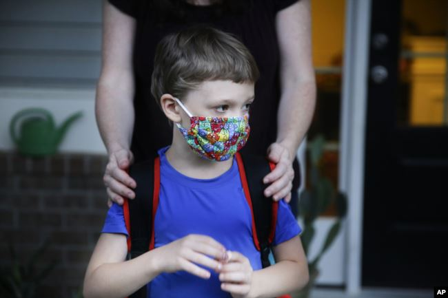 Rachel Adamus holds her son Paul, 7, in front of their house before the bus arrives for the first day of school on Monday, Aug. 3, 2020, in Dallas, Georgia, USA.