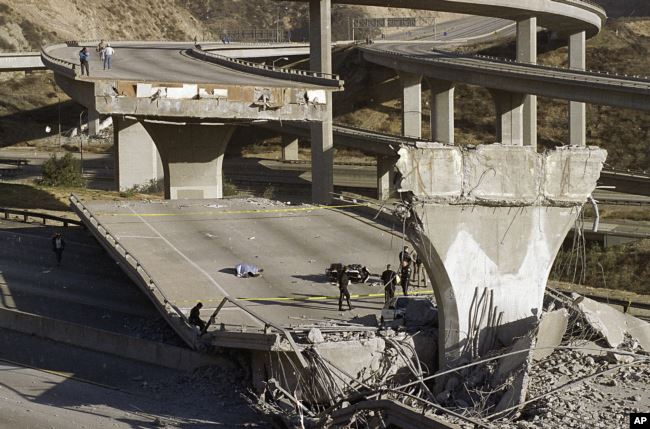 FILE - In this Jan. 17, 1994, file photo, the covered body of Los Angeles Police Officer Clarence Wayne Dean lies near his motorcycle which plunged off the State Highway 14 overpass that collapsed onto Interstate 5, after the Northridge earthquake.